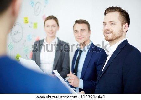 Young employee listening to one of colleagues opinion during discussion of working moments at start-up meeting