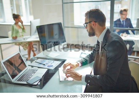 Young employee looking at computer monitor during working day in office #309941807