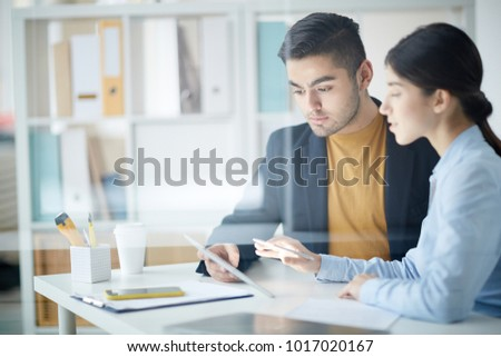 Young employee looking at touchpad display and listening to his colleague explanations of the data