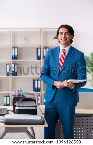 Young employee making copies at copying machine