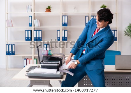Young employee making copies at copying machine  #1408919279