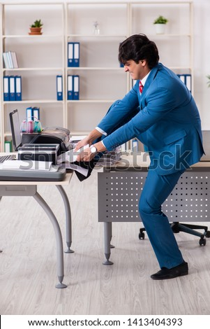 Young employee making copies at copying machine  #1413404393