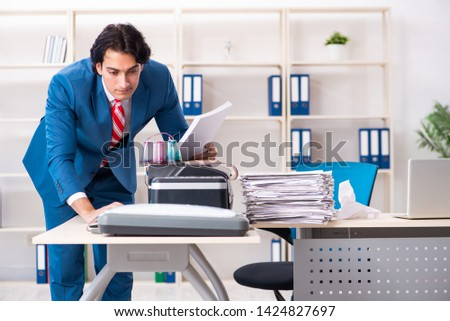 Young employee making copies at copying machine  #1424827697