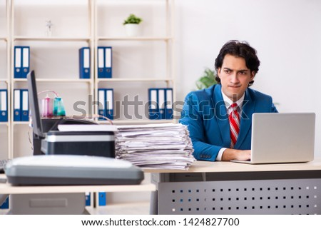 Young employee making copies at copying machine  #1424827700