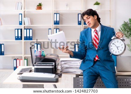Young employee making copies at copying machine  #1424827703