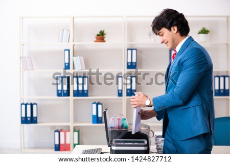 Young employee making copies at copying machine  #1424827712
