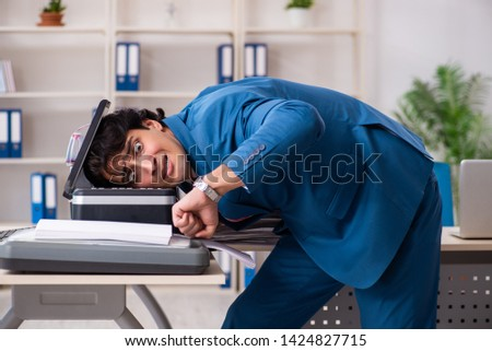 Young employee making copies at copying machine  #1424827715