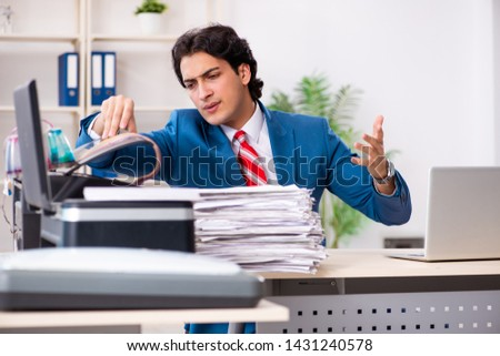 Young employee making copies at copying machine  #1431240578