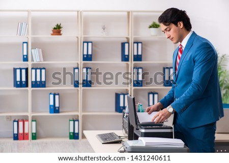 Young employee making copies at copying machine  #1431240611