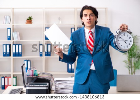 Young employee making copies at copying machine  #1438106813