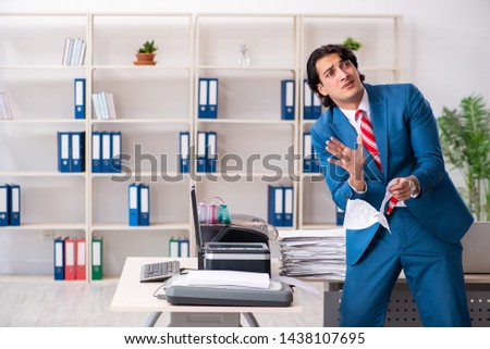 Young employee making copies at copying machine  #1438107695