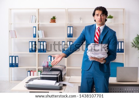 Young employee making copies at copying machine  #1438107701