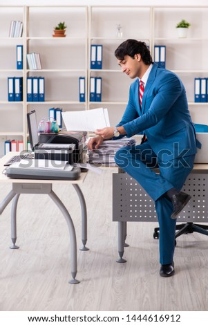 Young employee making copies at copying machine  #1444616912