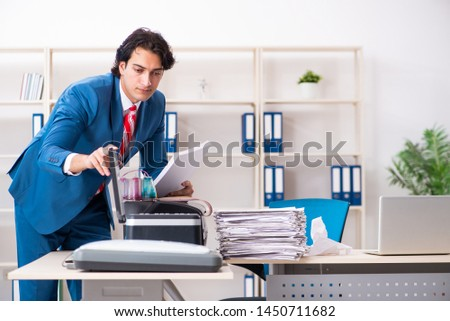 Young employee making copies at copying machine  #1450711682