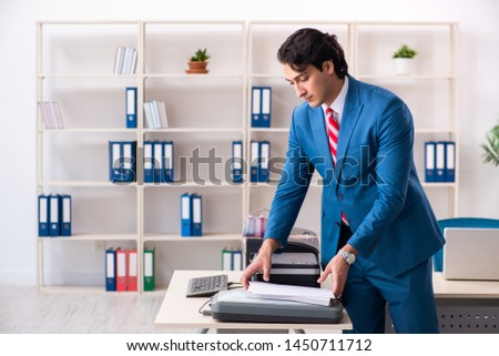 Young employee making copies at copying machine  #1450711712