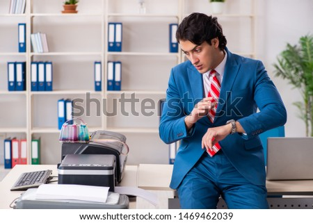 Young employee making copies at copying machine  #1469462039