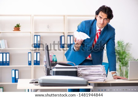 Young employee making copies at copying machine  #1481944844