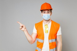 Young employee man in orange vest protective helmet mask coronavirus covid19 point finger aside on workspace isolated on grey background studio Instruments for renovation apartment Repair home concept