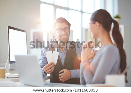 Young employee with two tickets offering his colleague to go to concert or performance in the evening