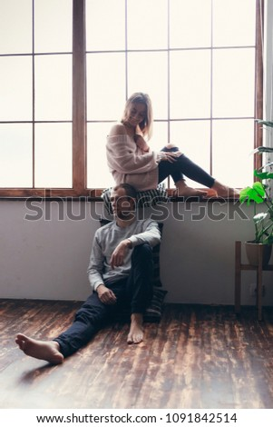 young enamored couple girl sitting on the windowsill, the guy on the floor, think litter, insult. in the room. concept love story #1091842514