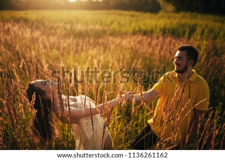 Young enamored couple have fun and smile at meadow against background of grass and spikes. Backlit. #1136261162