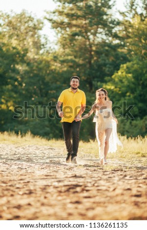 Young enamored couple holds hands and runs in forest against background of tree. #1136261135