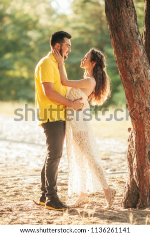Young enamored couple hugs in forest against background of tree. #1136261141