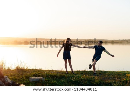 young enamored couple in nature in summer against the background of the river and sunset #1184484811
