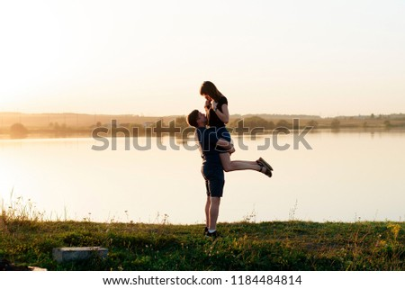 young enamored couple in nature in summer against the background of the river and sunset #1184484814