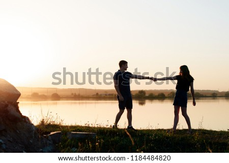 young enamored couple in nature in summer against the background of the river and sunset #1184484820