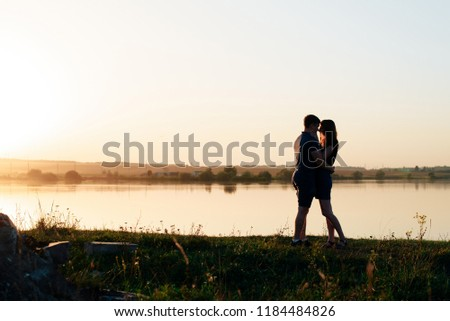 young enamored couple in nature in summer against the background of the river and sunset #1184484826