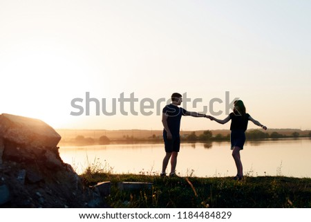 young enamored couple in nature in summer against the background of the river and sunset #1184484829