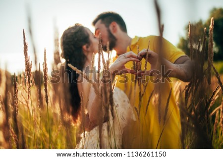 Young enamored couple kisses and makes shape of heart by their fingers at meadow against background of grass and spikes. #1136261150
