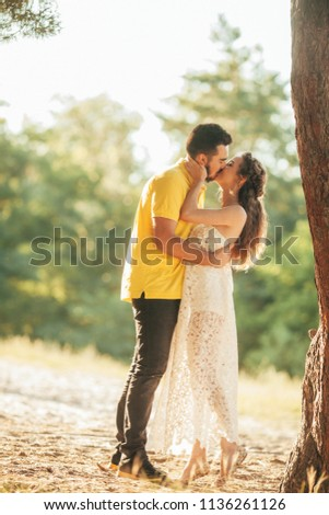 Young enamored couple kisses in forest against background of tree. #1136261126