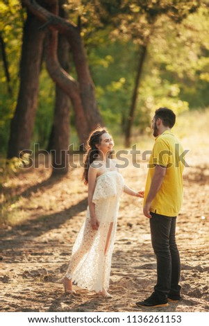 Young enamored couple smiles and holds hands in forest against background of trees. #1136261153