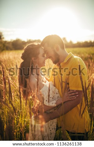 Young enamored couple smiles and hugs at meadow against background of grass and spikes. Backlit. #1136261138