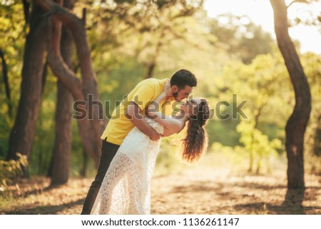 Young enamored couple smiles and hugs in forest against background of trees. #1136261147