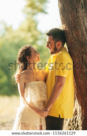 Young enamored couple smiles, hugs and holds hands in forest against background of tree. #1136261129