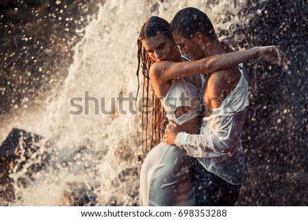 Young enamored wet couple hugs under spray and drops of waterfall. Around them are visible jets and streams of running water.  #698353288