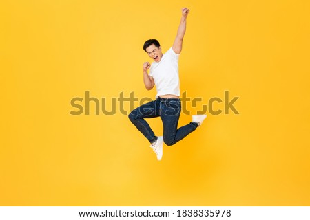 Young energetic Asian man  jumping and raising his fist isolated on yellow color background Сток-фото ©