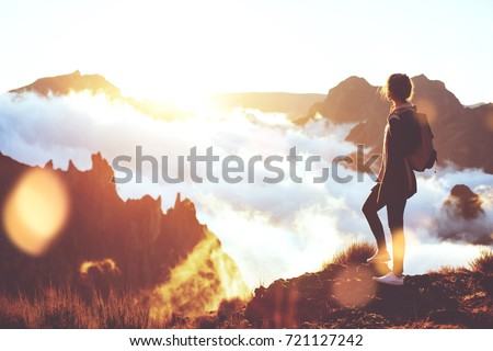 Young energetic girl with  backpack standing at edge of cliff in mountains and looking at sunset with a clouds.