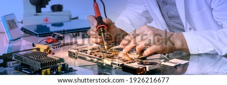 Young energetic male tech or engineer repairs electronic equipment in research facility. Shallow DOF, focus on the face and hands of the worker. Photo stock ©