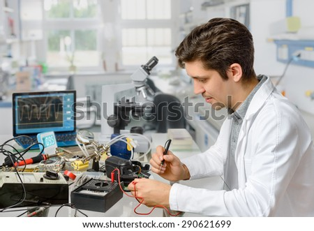 Young energetic male tech or engineer repairs electronic equipment in research facility. Shallow DOF, focus on the face of the worker. #290621699