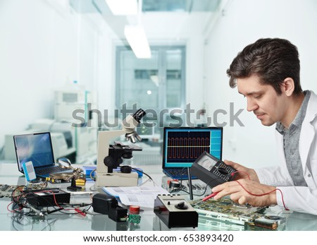 Young energetic male tech or engineer repairs electronic equipment in research facility. Shallow DOF, focus on the face of the worker. #653893420
