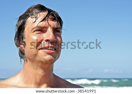 Young energetic man having fun at the beach - stock photo