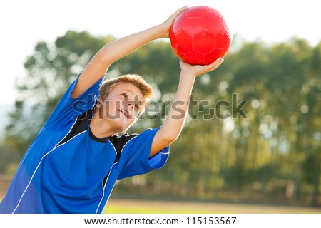 Young energetic teen boy jumping to red ball outdoors.