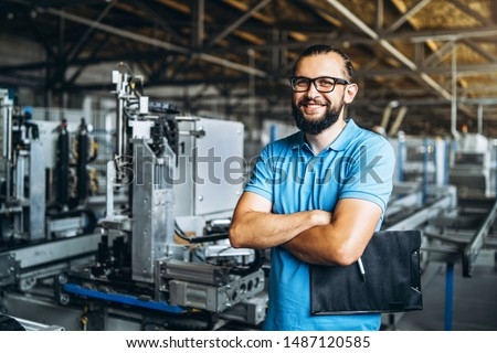 Young engeneer manager with beard checking manufactory, workplace and machinery in big factory