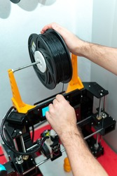 Young engineer adjusting 3D printer resin roll. Three-dimensional technology