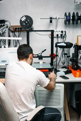 Young engineer adjusting 3D printer to print resin figures. Three-dimensional technology