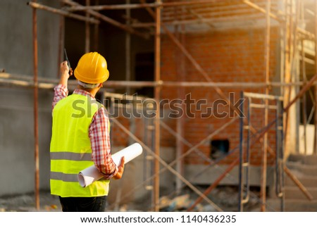 Young engineer blueprint  at construction site. #1140436235